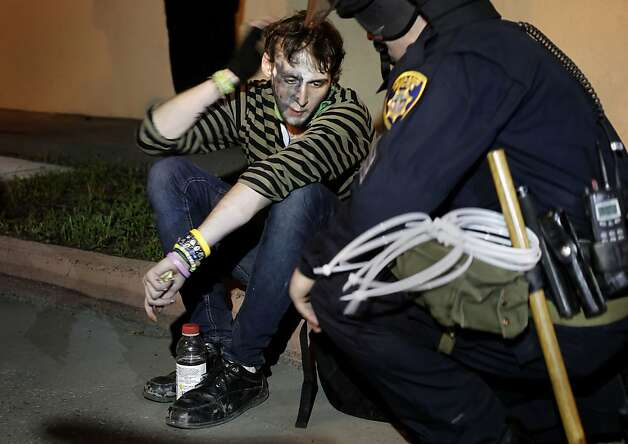 A protester seeks medical attention, unknown if he was under arrest, after Oakland police set up a perimiter on Broadway between 23rd and 24th streets and began arresting protesters with Occupy Oakland as they continued their march into the evening through the streets of downtown in Oakland, Ca. on Saturday January 28, 2012. Photo: Michael Macor, SFC