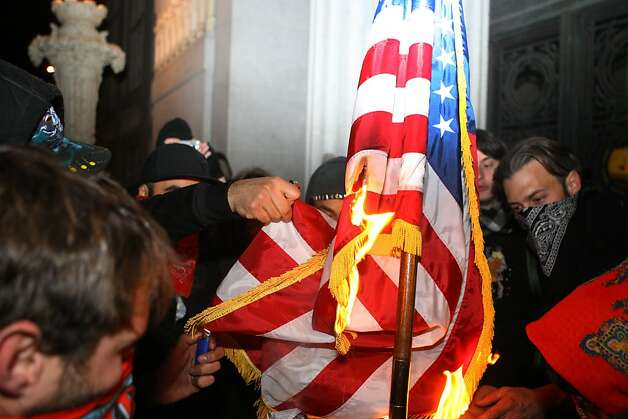 Occupy Oakland protesters help light up the American Flag after taking it from inside Oakland City Hall, Jan. 28, 2012. Photo: Erik Verduzco, The Chronicle
