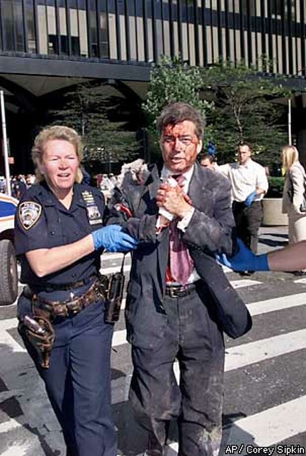 Police Officer Moira Smith leads injured Edward Nicholls, a broker at Aon Corporation, to safety from the burning World Trade Center in this file photo taken just before the collapse of the first tower on Sept. 11, 2001 in New York. Officer Smith was killed in the disaster minutes after this photograph was taken. Her remains were found in the ruins of the World Trade Center Wednesday, March 20, 2002. Photo: COREY SIPKIN