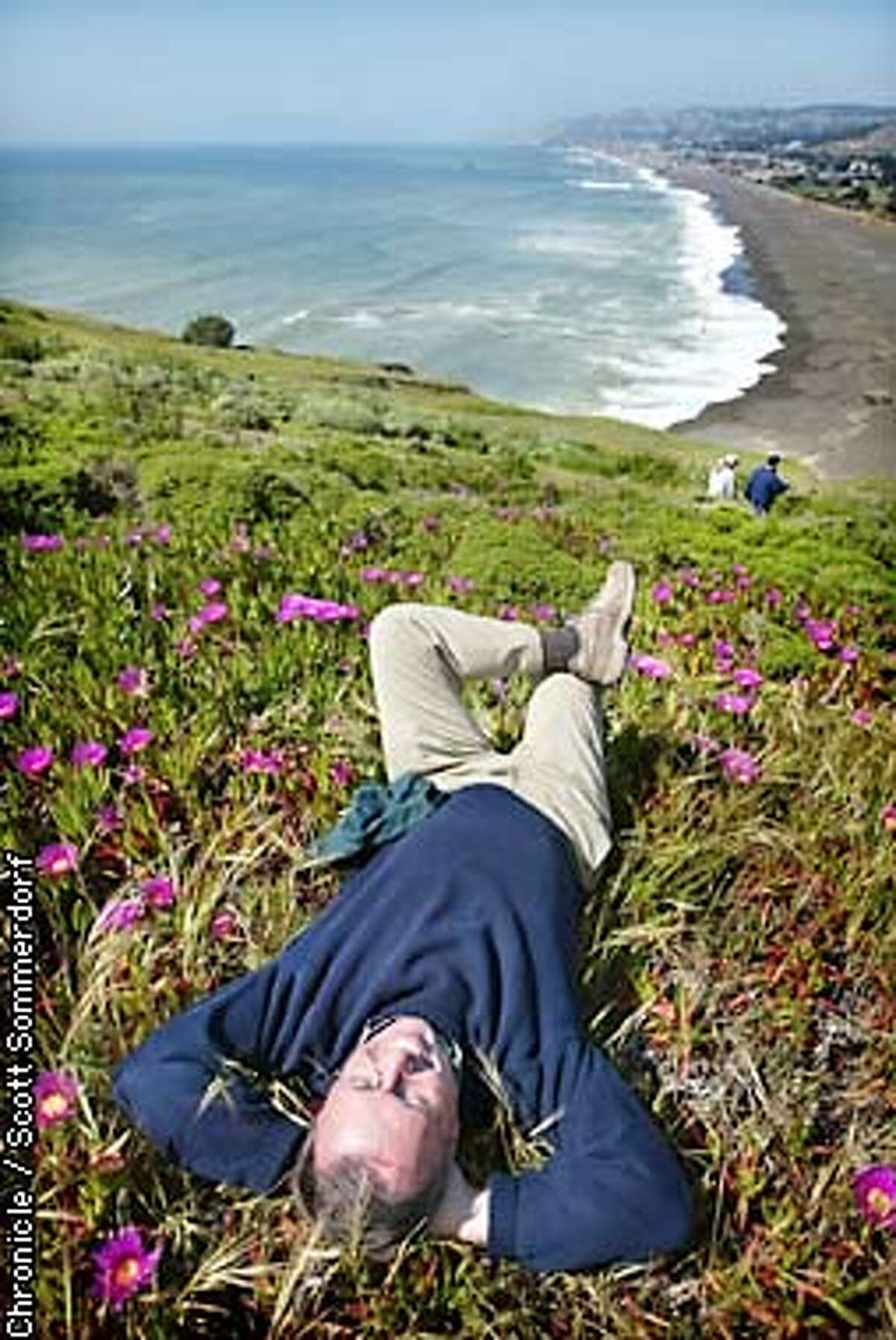 John reynolds, retiring head of the Nationasl Parks Department, relaxes on a hillside at the newest addition to the GGNRA - Mori Point near Pacifica. He says he is looking forward to more of these sorts of relaxing moments during his retirement. (SF CHRONICLE PHOTO BY SCOTT SOMMERDORF)