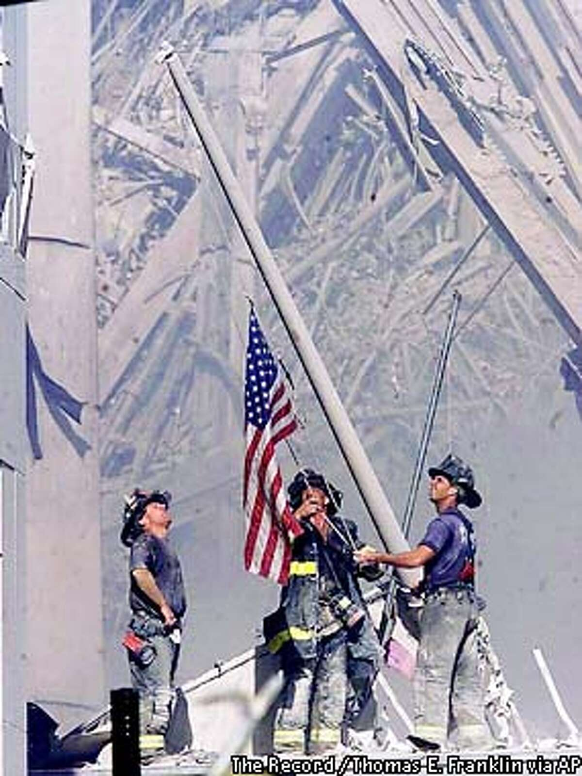 RETRANSMISSION TO ADD MAGAZINES OUT AND -- Firefighters raise a flag at the World Trade Center in New York Tuesday, Sept. 11, 2001, as work at the site continues after hijackers crashed two airliners into the center. (AP Photo/The Record, Thomas E. Franklin)MANDATORY CREDIT ALSO RAN 12/30/01