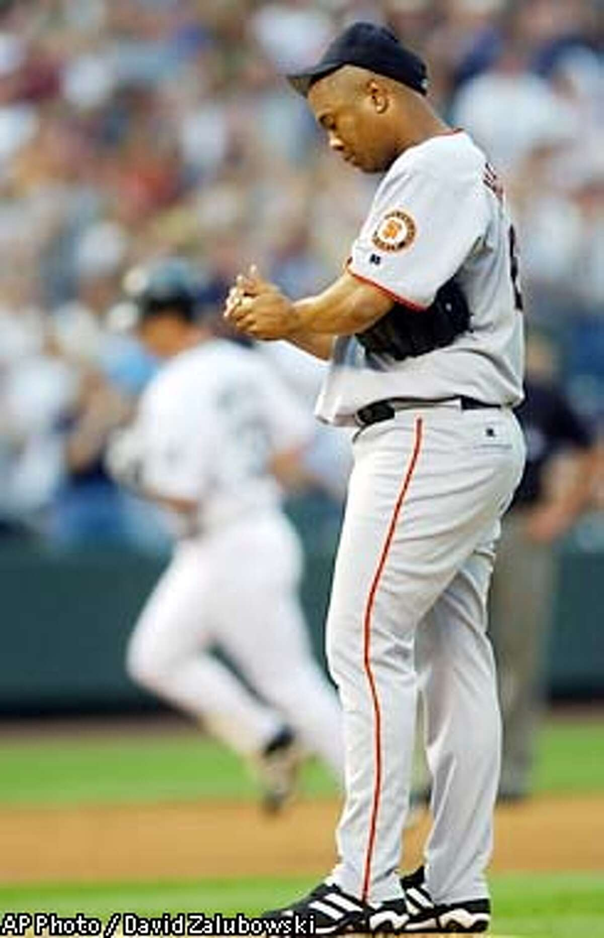 As Colorado Rockies' Larry Walker, back, circles the bases after hitting a three-run home run, San Francisco Giants starting pitcher Livan Hernandez rubs up a new ball in the second inning in Coors Field in Denver on Wednesday, July 3, 2002. Hernandez gave up seven runs in the inning before being pulled. (AP Photo/David Zalubowski)