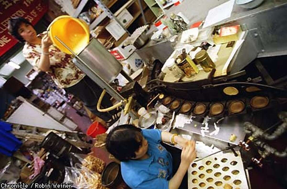 Nancy Tom, left, pours mixture into a machine where she and another worker, right, (who did not want to give her name) assemble fortune cookies at the Golden Gate Fortune Cookies store in China Town. BY ROBIN WEINER/THE CHRONICLE
