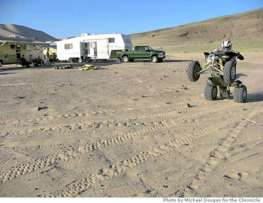An ATV passes the village of trailers that forms every weekend at the base of Sand Mountain, east of Fallon, Nevada. Photo by Michael Dougan, special to the Chronicle
