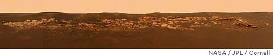 This high-resolution image captured by the Mars Exploration Rover Opportunity's panoramic camera highlights the puzzling rock outcropping that scientists are eagerly planning to investigate, released by NASA January 29, 2004. Presently, Opportunity is on its lander facing northeast; the outcropping lies to the northwest. These layered rocks measure only 10-centimeters (four-inches) tall and are thought to be either volcanic ash deposits or sediments carried by water or wind. Data from the panoramic camera's near-infrared, blue and green filters were combined to create this approximate, true-color image. EDITORIAL USE ONLY REUTERS/NASA / JPL / Cornell/Handout REUTERS 0 Photo: HO