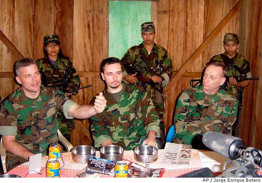 In this Friday, July 25, 2003 picture released Friday, Sept. 12, 2003, foreground from left, Keith Stansell, Marc Gonsalves and Tom Howes - three U.S. military contractors captured by the rebels seven months ago - sit inside a shack in an undisclosed place in southern Colombia, Friday, July 25, 2003 guarded by rebels of the Revolutionary Armed Forces of Colombia, FARC. Howes, Stansell and Gonsalves were reportedly on an intelligence mission for Pentagon contractor California Microwave Systems when their single-engine plane crash-landed in FARC-controlled territory on Feb.13. The rebels allegedly executed a fourth American and a Colombian soldier who were also aboard. (AP Photo/Jorge Enrique Botero) Photo: JORGE ENRIQUE BOTERO