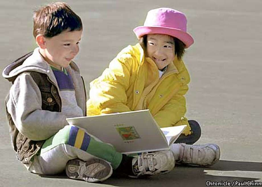 """Kindergartners Sam Gittleman and Lisa Chan read nursery rhymes on the playground. Jefferson Elementary School in the Sunset has received top marks with an """"A"""" rating.  PAUL CHINN/S.F. CHRONICLE Photo: PAUL CHINN"""