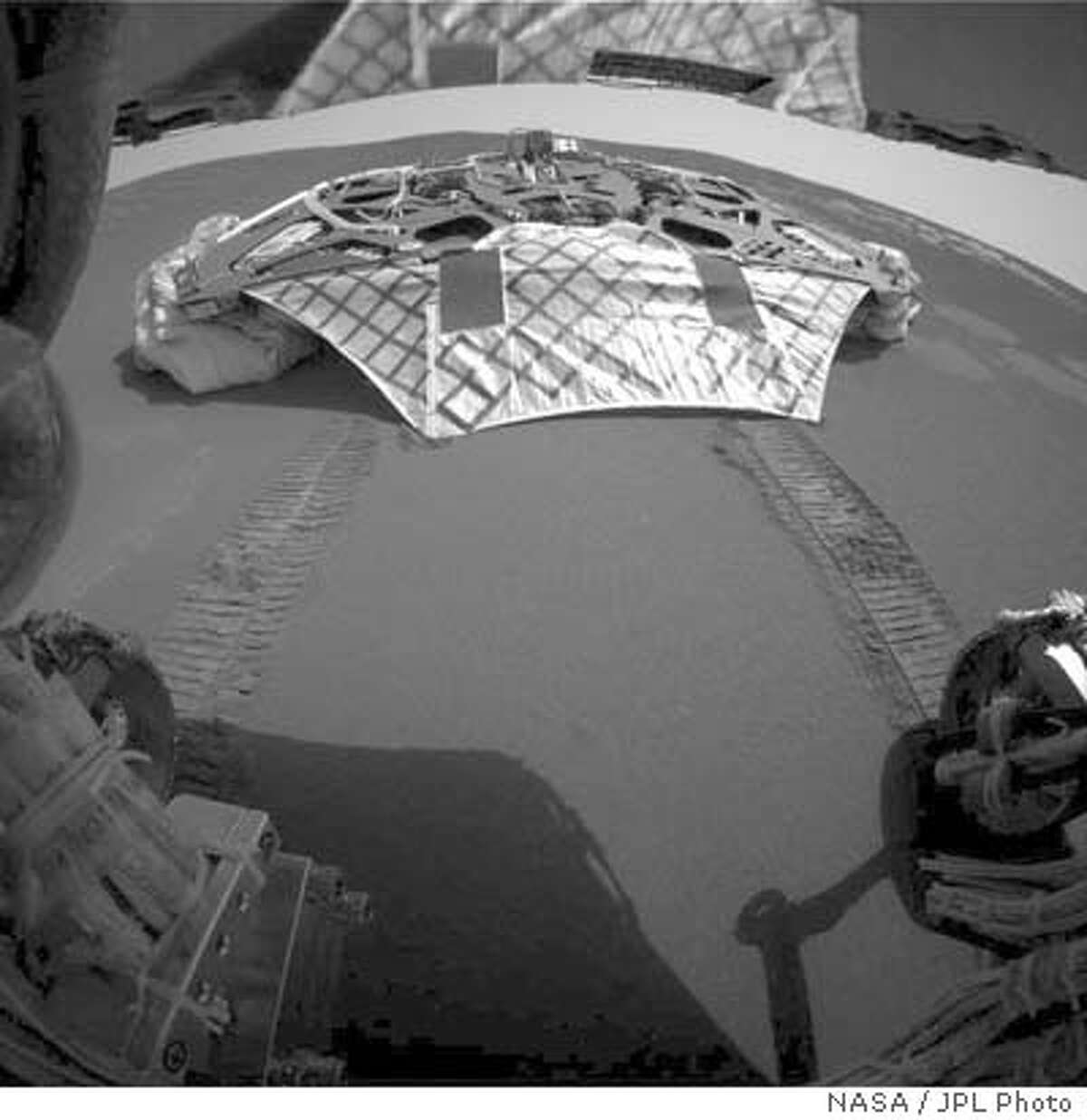 Opportunity rolled off the lander early Saturday morning and sent back a picture showing its tracks in the martian soil. NASA/JPL Photo