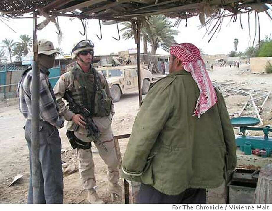 1st Lt. Brandon Burke of the 1st Armored Cavalry Division's 2nd Brigade, asks a local for information on insurgents in Abu Ghraib. Photo by Vivienne Walt, for the Chronicle