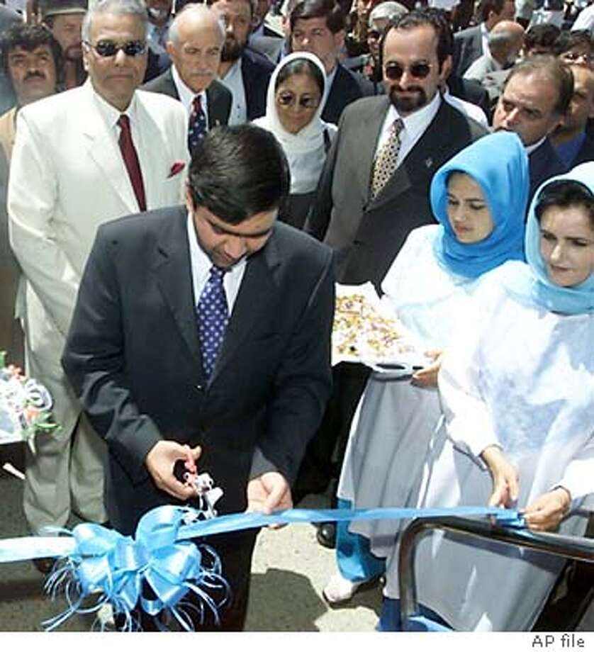 ** FILE ** Afghan Civil Aviation Minister Mirwais Sadiq cuts a ribbon in accepting an Airbus-300B4 aircraft, presented from India to Ariana Afghan Airlines, as Indian Foreign Minister Yashwant Sinha, in white suit, looks on during a ceremony in Kabul, Afghanistan, in this Aug. 10, 2002, file photo. Afghan aviation minister Mirwais Sadiq was assassinated Sunday March 21, 2004, in the western city of Herat, a government spokesman said. Gunmen shot Sadiq as he sat in his car in Afghanistan's main western city, presidential spokesman Khaleeq Ahmed said. (AP Photo/Amir Shah) Photo: AMIR SWHAH