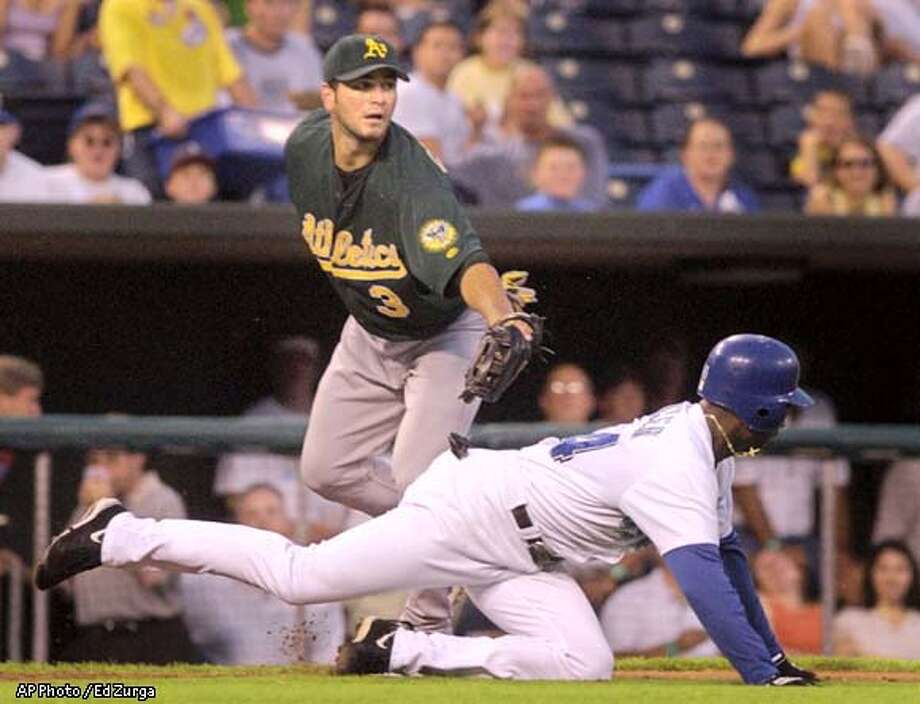 Oakland Athletics third baseman Eric Chavez, top, tags out Kansas City Royals' Michael Tucker during the second inning Monday, Aug. 26, 2002, in Kansas City, Mo. Tucker got caught in a rundown between third base and home plate after teammate Luis Ordaz grounded the ball to Athletics first baseman Scott Hatteberg. (AP Photo/Ed Zurga) Photo: ED ZURGA