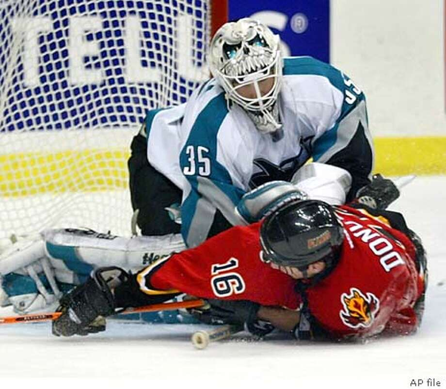 San Jose Sharks goalie Vesa Toskala, top, holds down Calgary Flames Shean Donovan after Donovan was tripped on a breakaway during second period NHL action in Calgary, Tuesday, Dec. 2, 2003. Donovan was awarded a penalty shot and scored. (AP Photo/Jeff McIntosh) Jonathan Cheechoo (right) gets crunched into the boards by Calgary's Chris Clark in the first period. Photo: JEFF MCINTOSH