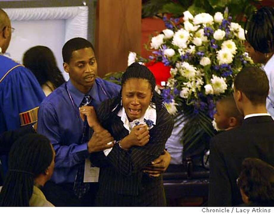 A family member consoles Chae Hughes, a relative of Scharod Fleming, after she views his body during the funeral service at the Third Baptist Church in San Francisco, Jan. 26, 2004. Funeral sevices for Scharod Fleming, 15 year-old who was shot to death last weekend at the underground promoter's hip-hop party, at the Third Baptist Church in San Francisco, Jan. 26, 2004. Lacy Atkins / The Chronicle Photo: Lacy Atkins