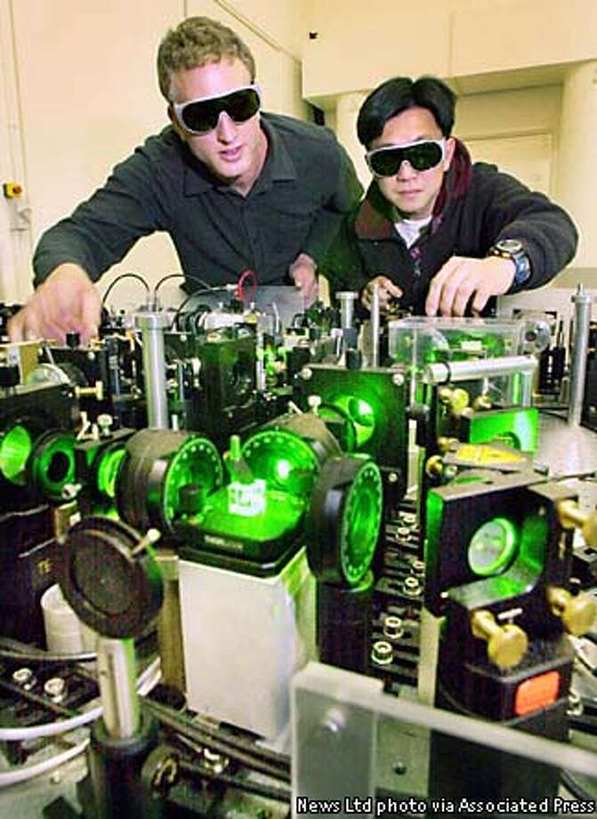 Thirty-four-year-old physicist Ping Koy Lam, right, and PhD student Warwick Bowen are seen during experiments at the Australian National University in Canberra Australia, Sunday, June 16, 2002. Using a process known as quantum entanglement, researchers led by Ping Koy Lam, have disassembled a laser at one end of an optical system and recreated a replica, a yard away in a dramatic technological break-through. (AP Photo/News Ltd)
