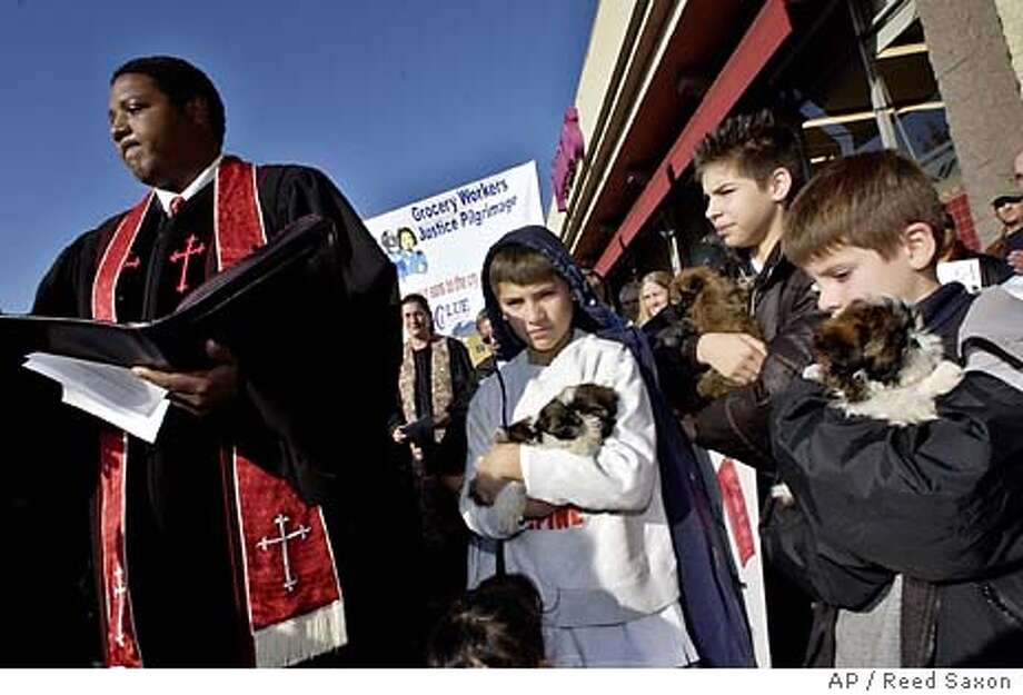 Glen Colson, 11, center, and his brothers Mark, 12, and Jonathan, 8, right, hold puppies as Pastor Palmerdon Palmer Jr. offers a blessing for the group at a sendoff rally for workers traveling to the Northern California home of Safeway CEO Steve Burd, at a Pavilions store in Los Angeles' Sherman Oaks neighborhood Tuesday, Jan. 27, 2004. Other workers were to join the group in Ventura and San Jose en route to hold a prayer vigil outside Burd's home in Alamo in the East Bay area in an effort to get talks in the four-month-old strike started again. The group said Burd is known for his philanthropy toward dogs. (AP Photo/Reed Saxon) Photo: REED SAXON