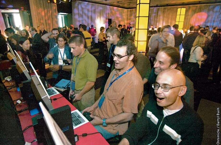 Harold Goldberg a reviewer for New York Entertainment Weekly, right, and David Thomas of the Denver Post, second from the right, play the online game NFL Game Day 2003 on computers at the Sony Gamers Day held in San Francisco. CHRONICLE PHOTO BY DARRYL BUSH Photo: Darryl Bush