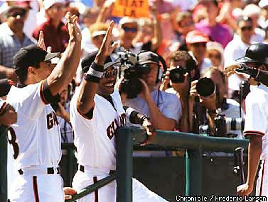 Dusty Baker (center) congratulates J.T. Snow after his fourth inning homer making the score 2 to 1 in the Giants' favor. BY FREDERIC LARSON/THE CHRONICLE Photo: FREDERIC LARSON