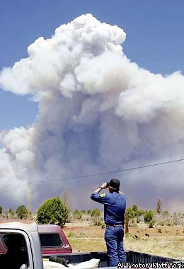 Jerry Young of the Navajo County Hash Knife Sheriff's Posse watches smoke billow from the Rodeo fire in Linden, Ariz., Thursday, June 20, 2002. The out-of-control wildfire crossed an area including a rural eastern Arizona town Thursday as it grew to as much as 60,000 acres, a fire spokeswoman said. (AP Photo/Matt York) Photo: MATT YORK