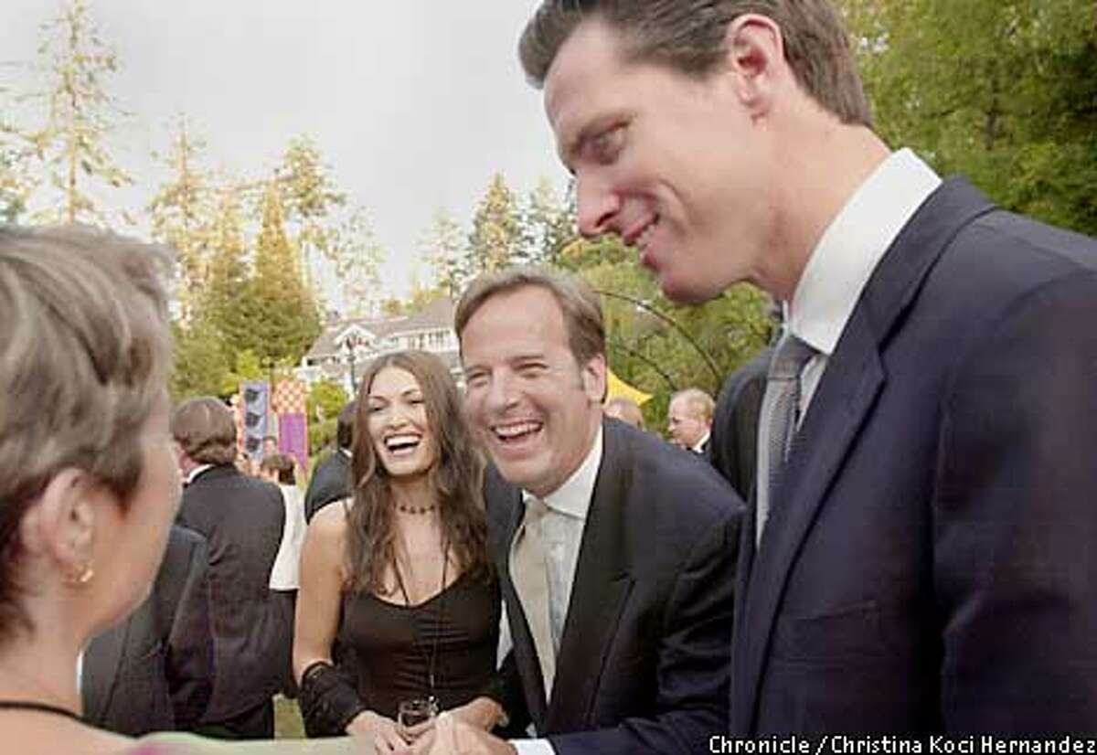 Kimberly Guilfoyle Newsom, left, John Conover and Gavin Newsom share a laugh at the Napa Valley Wine Auction, the world's largest charity wine event. Chronicle photo by Christina Koci Hernandez