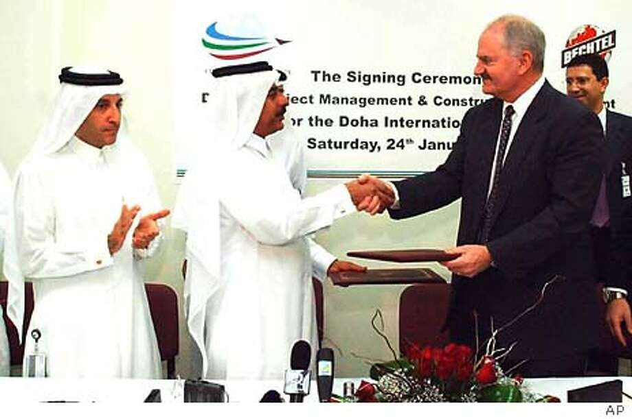 US engineering and project management company Bechtel Ltd Senior Vice President and Managing Director of Aviation Dr. James Van Hoften, right, and Qatar Aviation Authority Chairman Abdul Aziz Al Nuaimy exchange documents after signing a $2.5 billion contract to develop New Doha International Airport in Doha Saturday Jan. 24 2004. This will cost US$2.5 billion for phase one alone, said Qatar Airways Chief executive Akbar Al bakir, far left, looking on, at the ceremony held at Qatar Airways headquarters. (AP Photo) Photo: STR
