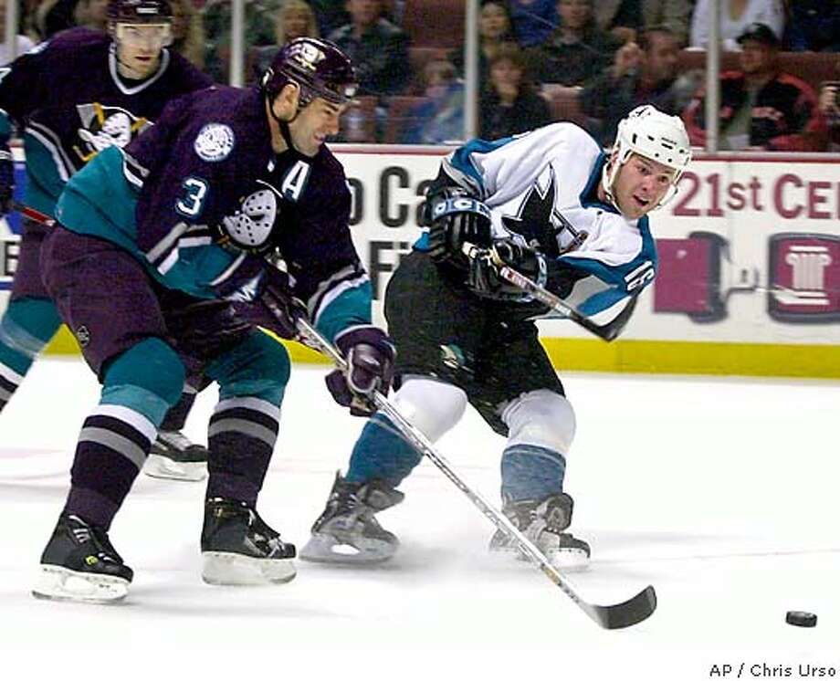 San Jose Sharks' Mark Smith (16) lets the puck fly to the goal while being chased down by Anaheim Mighty Ducks' Keith Carney (3) while Ducks' Martin Skoula, back, looks on during the first period on Friday, March 19, 2004 in Anaheim, Calif. Smith's shot found the net scoring a goal for the Sharks. (AP Photo/Chris Urso) Photo: CHRIS URSO