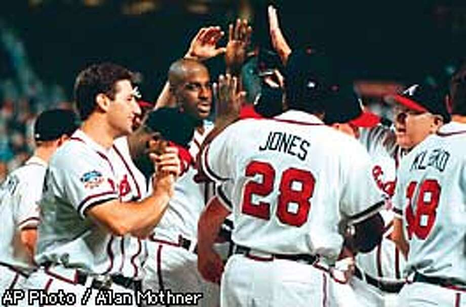 Atlanta Braves first baseman Fred McGriff, center, is mobbed by teammates after hitting a two-run, two out game winning home run off San Francisco Giants reliever Rod Beck in the bottom of the ninth inning Monday, Sept. 15, 1997, at Turner Field in Atlanta. The Braves defeated the Giants 5-4. (AP Photo/Alan Mothner) Photo: ALAN MOTHNER