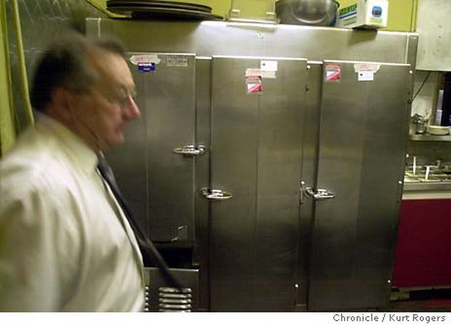 Joe Ursino walks past the old inefficient refrigerator at Dago Marys the only information on the refrigerator is that it says U.S.NAVY on it .  An Organization called SF Community Power Cooperative is replacing old inefficient refrigerators in bayview -hunters point with new ones . Event on 1/9/04 in San Francisco. KURT ROGERS / The Chronicle Photo: KURT ROGERS