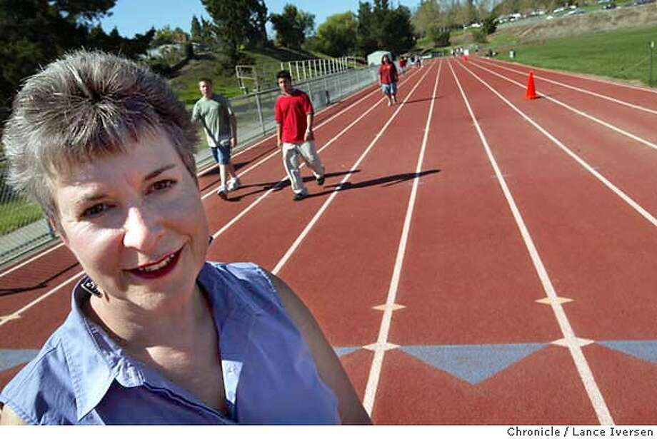 SCHOOLS064_LI.JPG  event on 3/17/04 in PLEASANT HILL Dawn Block is a College Park parent who made a contribution of 5000 shares of stock to fund a $400,000 all weather track at Pleasant Hill�s College Park High School a few years ago poses for a photo as a PE class walks laps on the track. Dawn also headed a fundraiser to build two storage buildings on campus to house all the track equipment that she and other parents funded. By  Lance Iversen/The San Francisco Chronicle Photo: Lance Iversen
