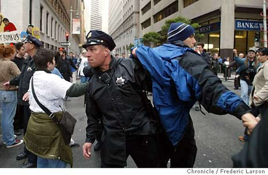 An unidentified protester is removed form an intersection Friday, March 14, 2003 in San Francisco. After failing to close the Pacific Stock Exchange, anti-war protesters did shut down a major financial district intersection before police began making dozens of arrests. (AP Photo/San Francisco Chronicle, Frederic Larson) Photo: FREDERIC LARSON