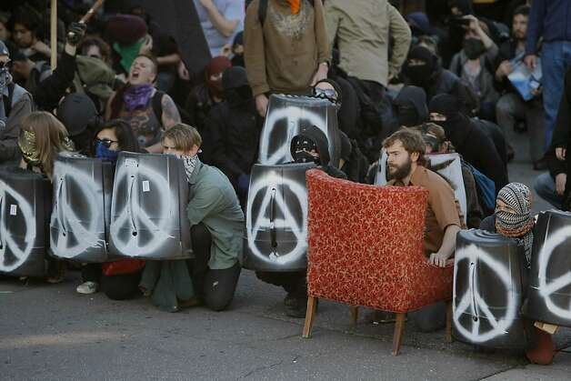 Occupy Oakland protesters take cover behind plastic shields after police fired non-lethal weapons near Oak and 10th Streets in Oakland, Calif., Jan. 28, 2012. Photo: Erik Verduzco, The Chronicle
