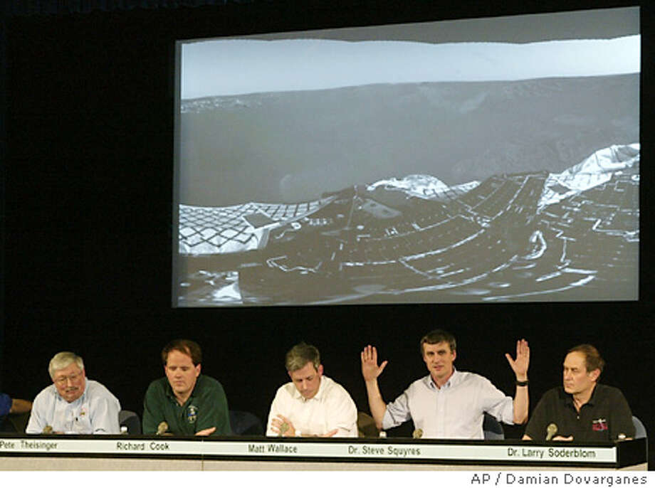 "Steve Squyres, second from right, principal investigator, Cornell University describes the latest images transmitted from the rover ""Opportunity"" from Mars landscape during a news conference at the Jet Propulsion Laboratory in Pasadena, Calif. on Sunday 25, Jan. 2004. The unmanned, six-wheeled rover landed at 9:05 p.m. PST in Meridiani Planum, NASA said. The smooth, flat plain lies 6,600 miles and halfway around the planet from where its twin, Spirit, set down on Jan. 3. From left to right: Pete Theisinger, Mars Exploration Rover (MER) project manager, Richard Cook, MER deputy project manager, Matt Wallace, MER deputy surface development manager, Steve Squyres, principal investigator, Cornell University and Larry Soderblom, US Geological Survey.(AP Photo/Damian Dovarganes) Photo: DAMIAN DOVARGANES"