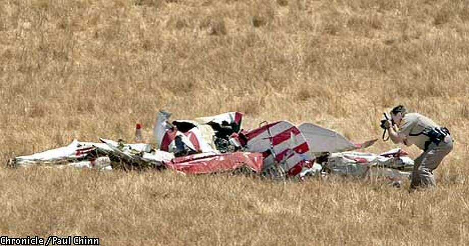 (UNCORRECTED COLOR IMAGE)  Contra Costa Co. sheriffs Sgt. Craig Stevens photographed the wreckage of a stunt plane which crashed killing the pilot on a hillside near Empire Mine Rd. and Deer Valley Rd. south of Antioch  PAUL CHINN/S.F. CHRONICLE Photo: PAUL CHINN