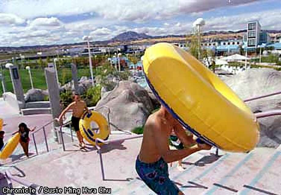 """PREWETT1/C/14SEP97/CC/SMHC  Kids haul their water tubes up the stairs to the """"Canyon Cooler"""" slide at Prewett Water Park in Antioch. CHRONICLE PHOTO BY SUSIE MING HWA CHU."""