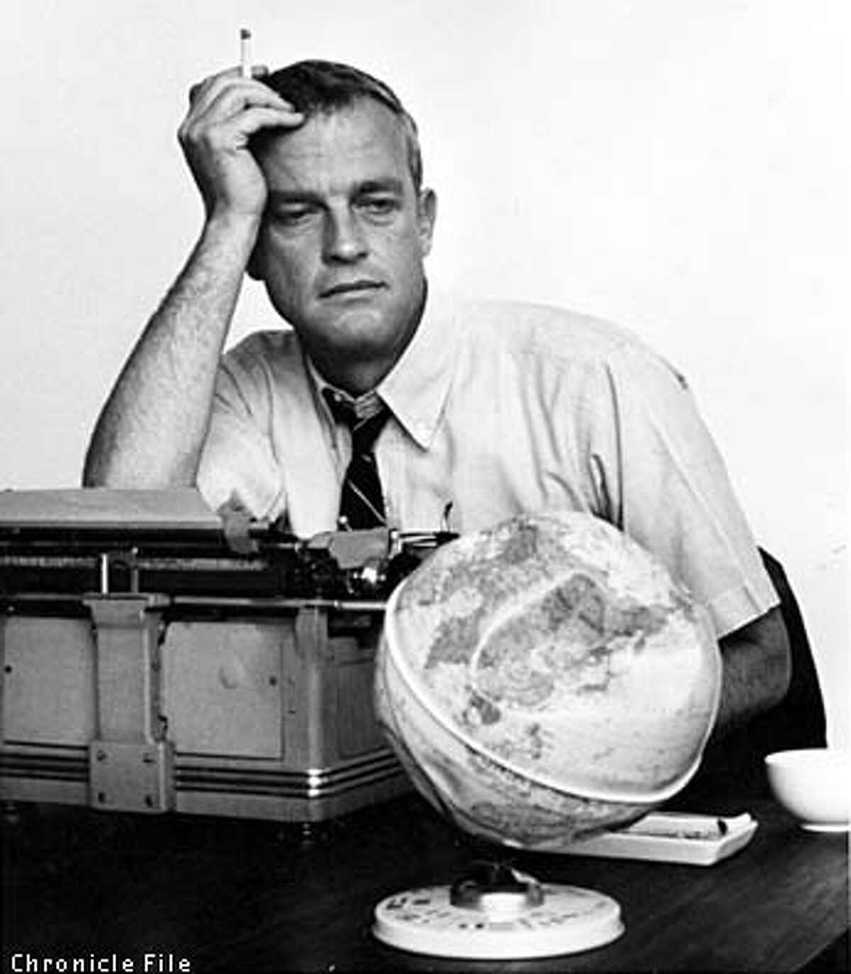 Art Hoppe wrestles with verbs and nicotine at his desk in 1966. Chronicle File Photo