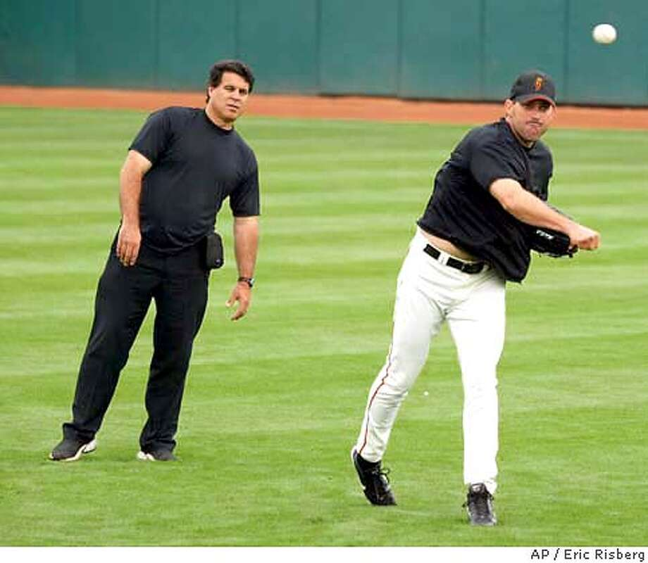 Injured San Francisco Giants' closing pitcher Robb Nen, right, throws in the outfield of Scottsdale Stadium as Giants' trainer Stan Conte, left, looks on prior to the Giants' spring training game against the Oakland Athletics in Scottsdale, Ariz., Saturday, March 13, 2004. Nen, who has been injured since 2002, hopes to resume pitching after the season begins.(AP Photo/Eric Risberg) Photo: ERIC RISBERG