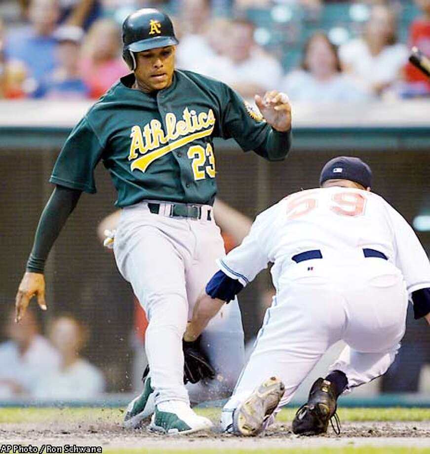 Oakland Athletics runner David Justice, left, tags home plate as Cleveland Indians pitcher Jason Phillips tries to make the tag in the second inning Thursday, Aug. 22, 2002 at Jacobs Field in Cleveland. Justice was safe on the play.(AP Photo/Ron Schwane) Photo: RON SCHWANE