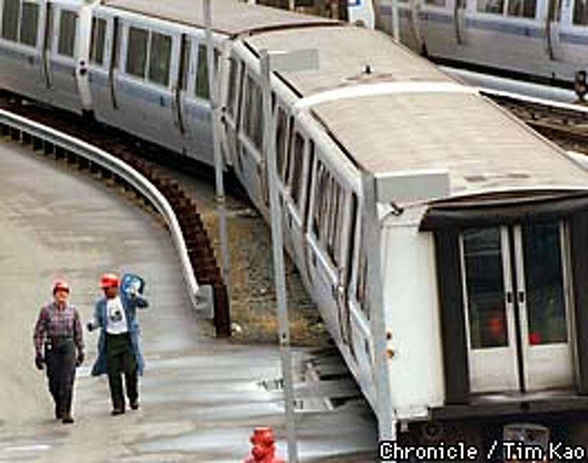In this file photo, BART workers walk near BART cars at the Colma station.