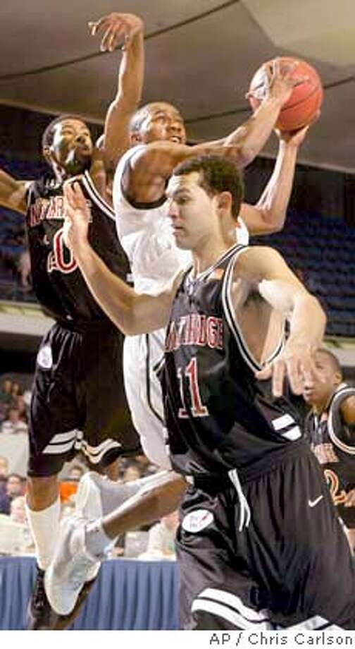 Pacific's Miah Davis goes to the basket between Cal State Northridge's Joseph Frazier, left, and Ian Boylan during the first half in the championship game of the Big West men's tournament in Anaheim, Calif., on Saturday, March 13, 2004. (AP Photo/Chris Carlson) Photo: CHRIS CARLSON