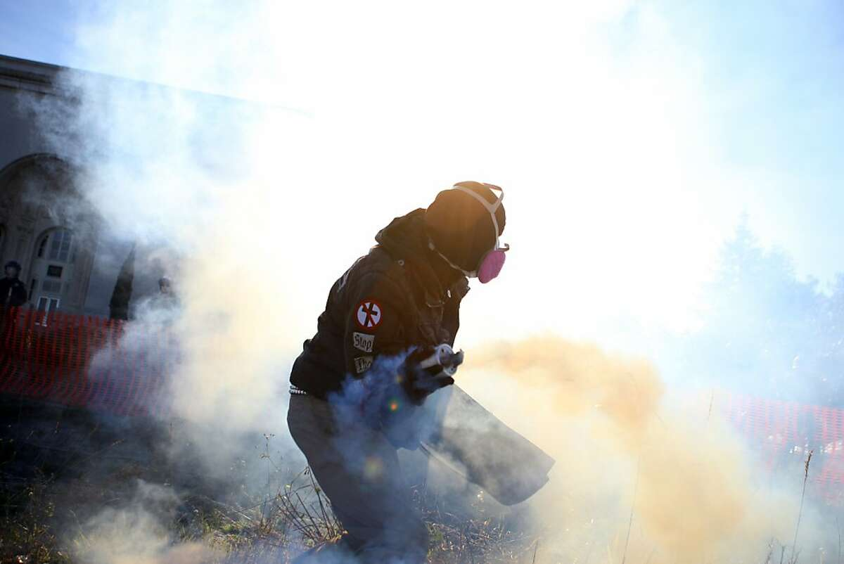 A protesters throws back a can of smoke that Oakland police officers fired at protesters after refusing to disperse near Laney College in Oakland, Calif., Jan. 28, 2012.