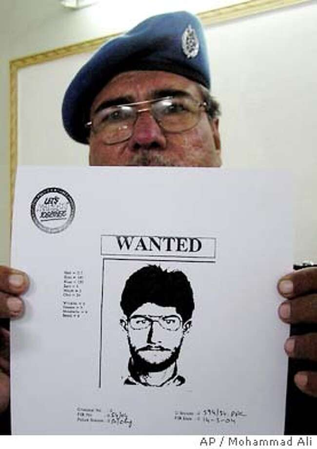 A Pakistani police officer shows a sketch of suspect who snatched a vehicle which was found next to the U. S. consulate, containing a water tank, filled with explosives in Karachi, Pakistan Monday, March 15, 2004, after police explosive experts disconnected a timer and detonators attached to the tank. Police said. It was not immediately clear who planted the device. (AP Photo/Mohammad Ali) A Pakistani soldier checks a van that held explosives and detonators in Karachi, Pakistan. Photo: MOHAMMAD ALI