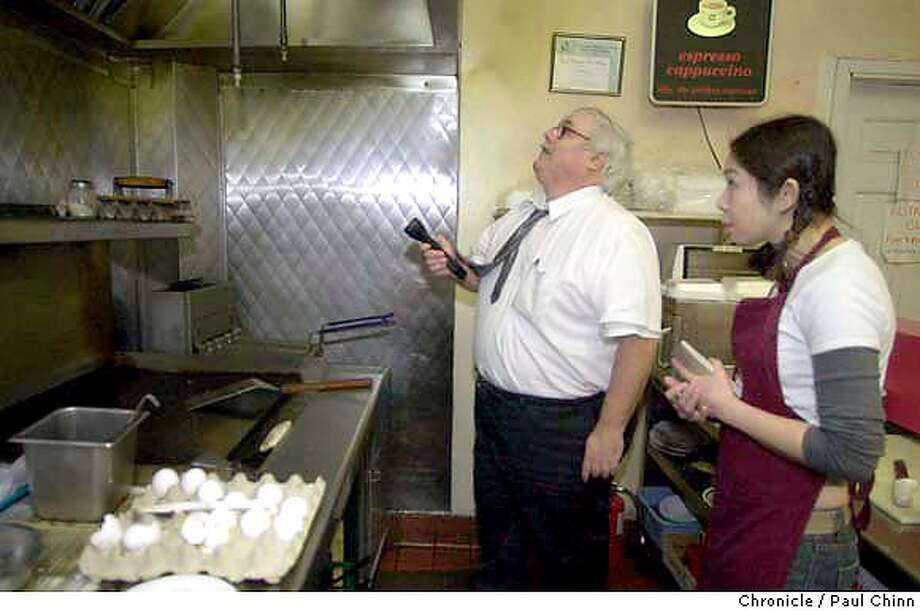 Ed Walsh checks the vent over the grill as cook Jenny Chau takes a look. City health inspector Ed Walsh inspects restaurants in San Francisco on 1/20/04. PAUL CHINN / The Chronicle CcCCC ProductNameChronicle ProductNameChronicle CcCCC Photo: PAUL CHINN