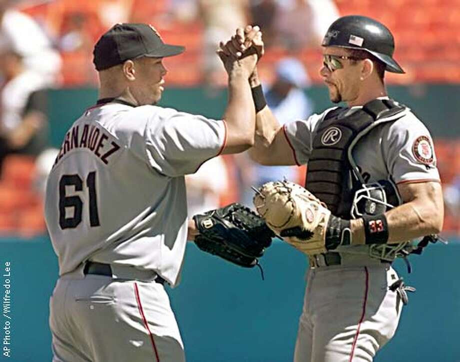 San Francisco Giants pitcher Livan Hernandez (61) and catcher Benito Santiago, right, congratulate each other after defeating the Florida Marlins 3-0. Monday, Aug. 19, 2002 in Miami. (AP Photo/Wilfredo Lee) Photo: WILFREDO LEE