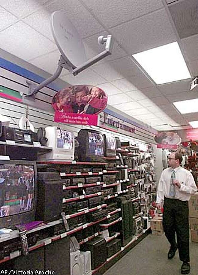 SATELLITE TV / FOR USE ANYTIME--An unidentified electronics store employee peruses the electronics shelf as a Primestar satellite hangs near the ceiling Dec. 24, 1998 in Los Angeles. Satellite companies have set out to snare more customers by joining forces with local phone companies and using some decidedly low-level technology that lets satellite customers watch local channels. (AP Photo/Victoria Arocho) Photo: VICTORIA AROCHO