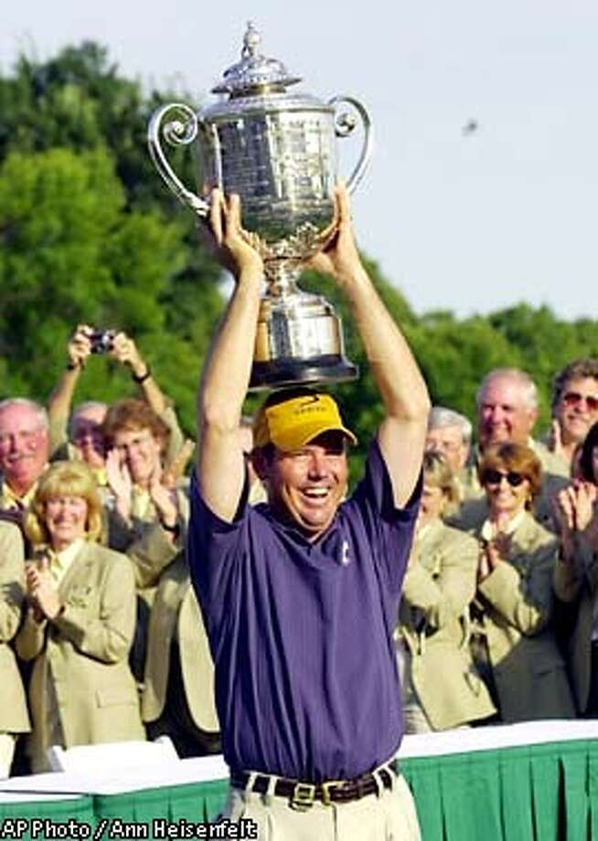 Rich Beem hoists the Wanamaker Trophy after capturing the 84th at Hazeltine National Golf Club in Chaska Minn., on Sunday, Aug. 18, 2002. Beem finished at 10-under 278, one stroke ahead of Tiger Woods. (AP Photo/Ann Heisenfelt) Photo: ANN HEISENFELT