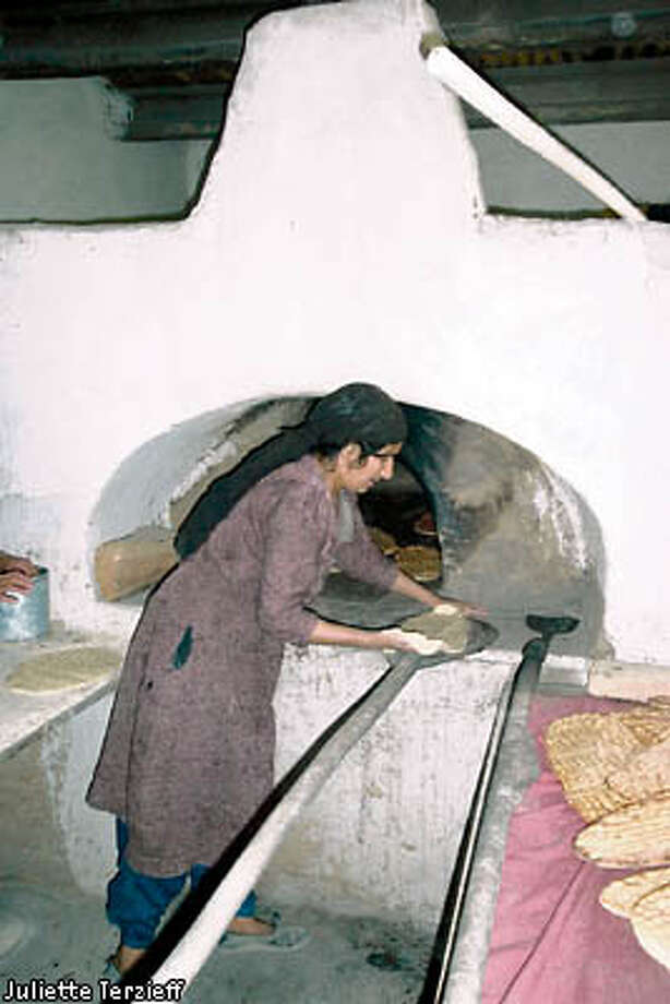 An Afghan woman in one of Kabul's 21 widow's bakeries prepares to put bread in the oven to bake. Photo by Juliette Terzieff, special to the Chronicle