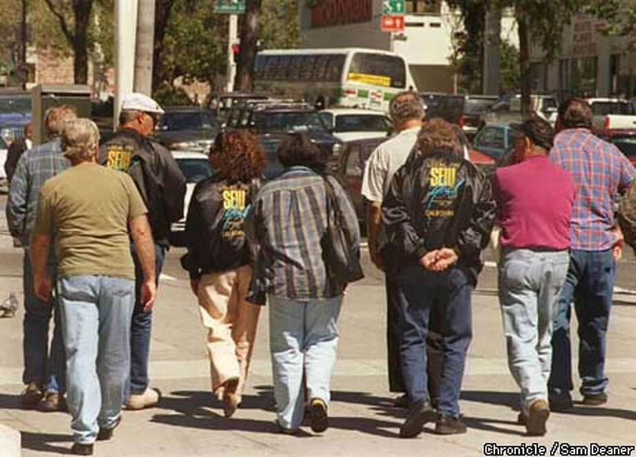 BART-MEET 2/C/09SEP97/MN/SD  Union workers walk down Van Ness Street at the War Memorial building while informal negotiations are underway betrween BART officials and the Union at Mayor Willie Brown's office. (Chronicle Photo bySam Deaner)