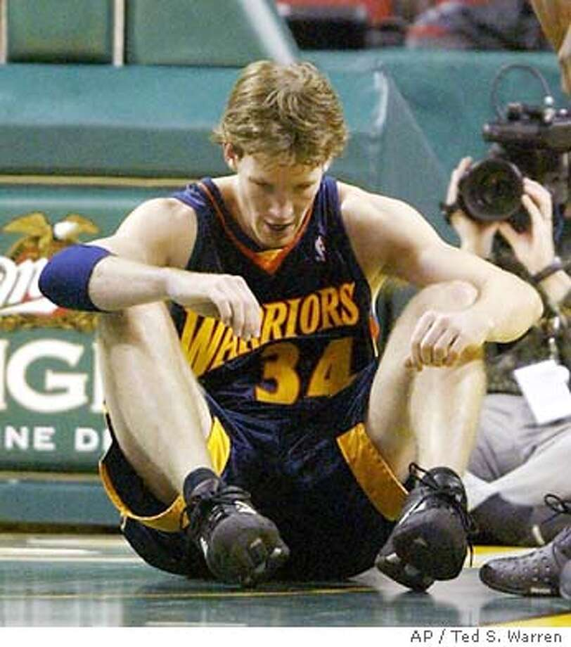Golden State Warriors forward Mike Dunleavy sits on the court in the first quarter after being charged with a foul against Seattle SuperSonics' Calvin Booth on Thursday, Jan. 22, 2004, in Seattle. (AP Photo/Ted S. Warren) Photo: TED S. WARREN