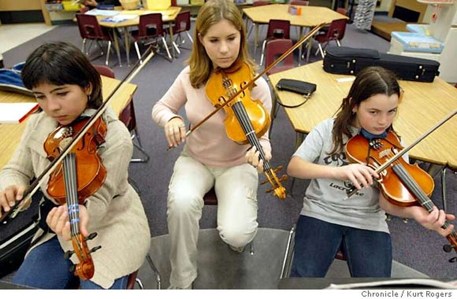 Lauren Berger (center) a 10th grader at Carlmont High school helps Vivian Klein and Stephanie Merenbach both 5th graders at Central Elementary with their violins.  Carlmont High schoolers in belmont are volunteering their time after school teaching elementary school students to read music and play instrumentsPNMUSIC_kr124.JPG Event on 1/13/04 in Belmont . KURT ROGERS / The Chronicle Photo: KURT ROGERS