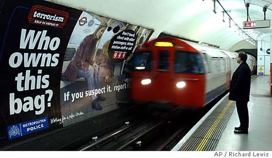 A passenger stands opposite an anti terrorism poster as a train pulls into London's Embankment tube station, Monday, March 15, 2004. The poster is part of a heightened awareness campaign, which follows on from the terror train bombs in Spain last week. (AP Photo/Richard Lewis) An anti-terrorism poster in the Embankment station is part of a heightened awareness campaign in the London Underground after the train bombings in Spain last week. Photo: RICHARD LEWIS