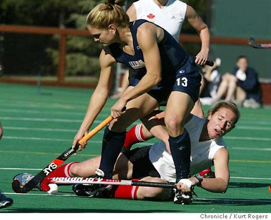 US team in Blue #13 Keli Smith and Canada's Andrea Rushton gets tangled up during first half play .  US vs. Canada in field hockey. this is the Olympic team, trying to earn an Olympic berth. Event on 1/21/04 in Palo Alto. KURT ROGERS / The Chronicle Photo: KURT ROGERS